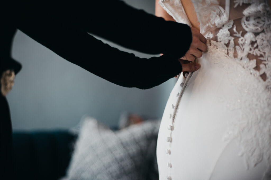 Bride getting fitted into a bridal gown by a bridal consultant